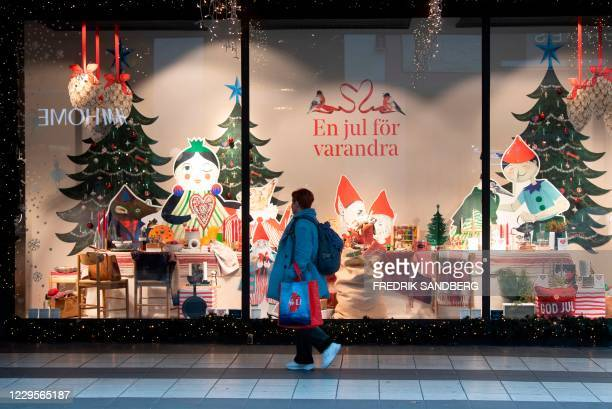 Woman passes a Christmas decorated shopping window in central Stockholm on November 10 amid the novel coronavirus COVID-19 pandemic. / Sweden OUT