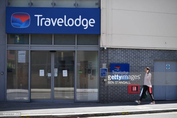 A woman passes a closed Travelodge hotel in Redhill southeast of London on June 5 2020 The Travelodge hotel chain are seeking £144m rent cuts from...