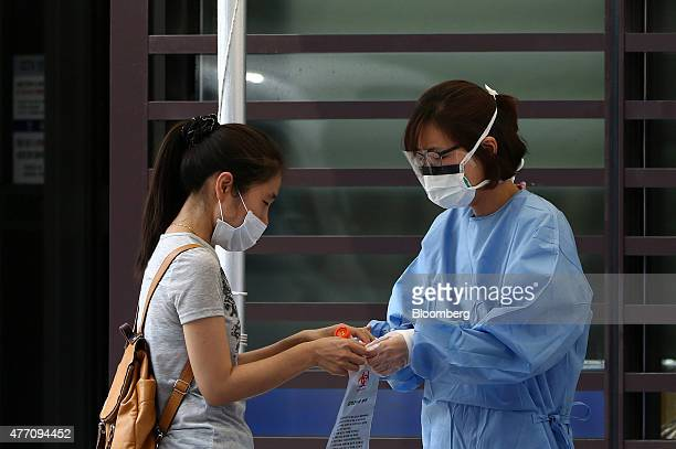 A woman passes a container of her saliva sample to a member of the medical staff to check for Middle East Respiratory Syndrome infection at Samsung...