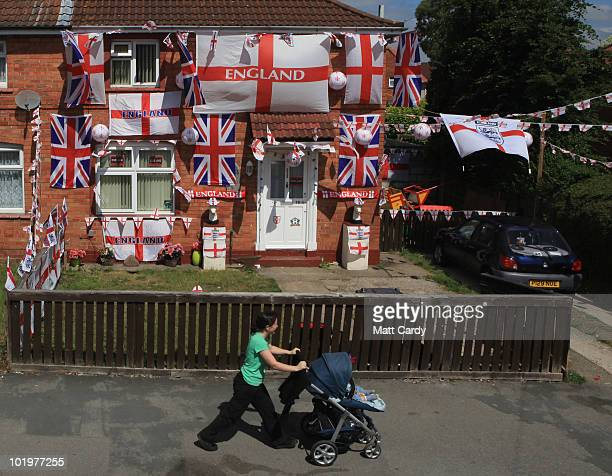 A woman passes a house covered in England flags in a street in the Knowle West area on June 11 2010 in Bristol England Although the 2010 FIFA World...