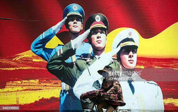 A woman passes a military propaganda poster on a street in Shanghai on July 12 2016 Beijing braced on July 12 for an international tribunal's ruling...