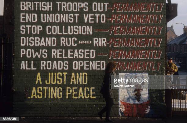 Woman passes a mural on the corner of The Falls Road, the heart of the Catholic and Republican community of west Belfast, 23rd December 1994. The...