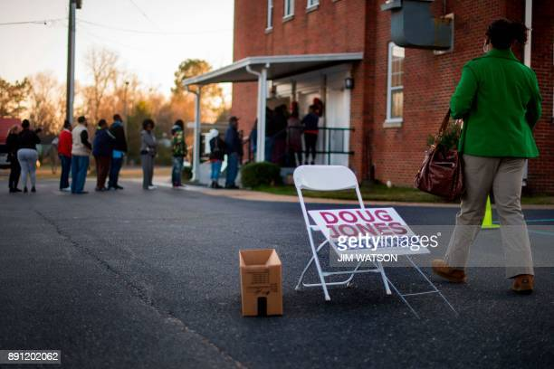 A woman passes a placard for Democratic Senatorial candidate Doug Jones as she walks over to get in the long line to vote at Beulah Baptist Church...