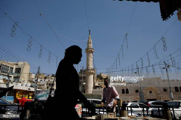 A woman passes a street vendor and a minaret in Amman Jordan on Thursday June 21 2018 President Trump and First Lady Melania Trump will host...