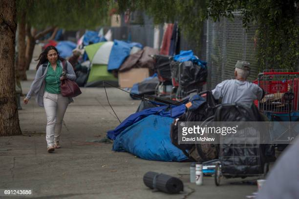 A woman passes a wheelchairbound homeless man on Spring Street on May 1 2017 in Los Angeles California The newly released 2017 Greater Los Angeles...