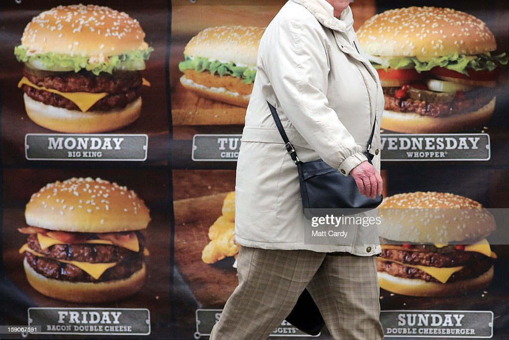 A woman passes an advertisement outside a fast food outlet on January 7, 2013 in Bristol, England. A government-backed TV advert - made by Aardman, the creators of Wallace and Gromit - to promote healthy eating in England, is to be shown for the first time later today. England has one of the highest rates of obesity in Europe - costing the NHS 5 billion GDP each year - with currently over 60 percent of adults and a third of 10 and 11 year olds thought to be overweight or obese.