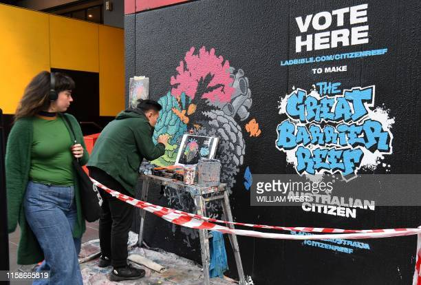 A woman passes artist Ed Wong as he paints a mural depicting coral in the shape of an anatomical heart with half of the heart deteriorating...