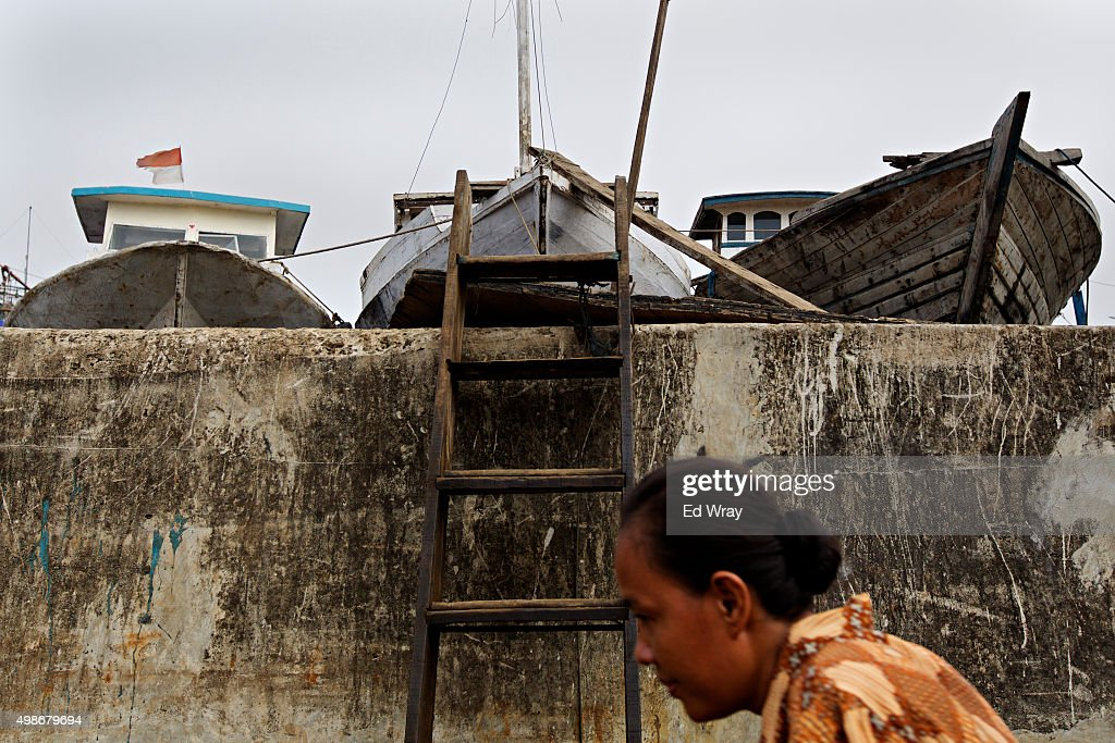 A woman passes below a seawall in an area more lying more than a meter below sea level in the Maura Baru district November 24, 2015 in Jakarta, Indonesia. Jakarta, Southeast Asia's largest city is sinking slowly into the sea, largely due to overconsumption of ground water. Experts say that if nothing is done, the city's northern coast will be inundated with 5-7 meters (15-21 ft.) of seawater by the year 2080. The city has begun shoring up its sea defenses as increasing floods and severe storms due to rising temperatures and climate change threaten the mostly poor residents of Jakarta's northern coast with the loss of their homes.