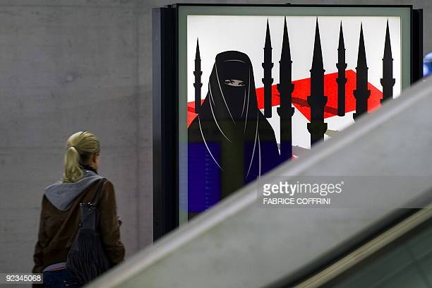 A woman passes by a campaign poster of the farright Swiss People's Party depicting a woman wearing a burqa against a background of a Swiss flag upon...