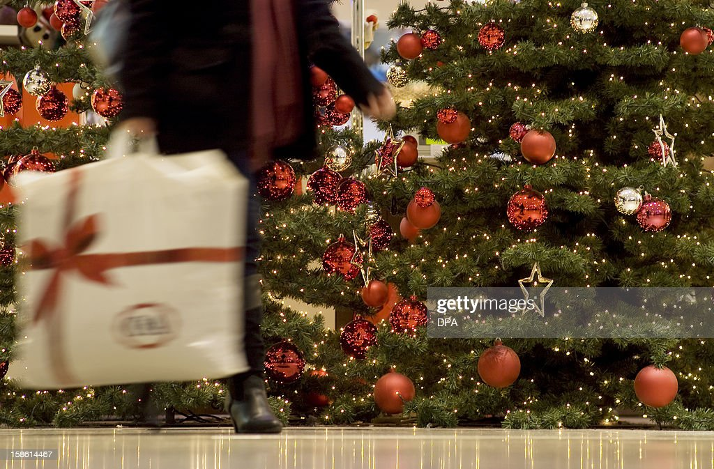 A woman passes by a christmas tree in a shopping mall in Berlin, on December 20, 2012. Retailers expect a growth in the Christmas sales. AFP PHOTO / Inga Kjer GERMANY OUT