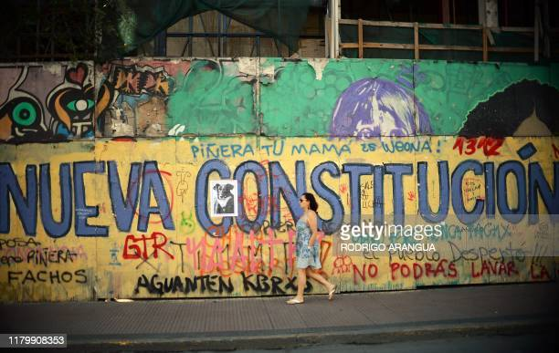 TOPSHOT A woman passes by a graffiti that reads New Constitution in Santiago on November 03 2019 Protesters angry about the cost of living and a...
