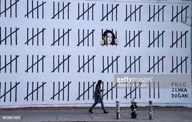 A woman passes by a new 70footlong mural by anonymous British artist Banksy on March 16 2018 that was unveiled on March 15 2018 at the corner of...