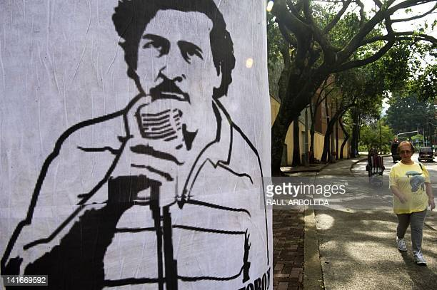 Woman passes by a poster with the image of deceased Colombian drug lord Pablo Escobar along a street of Medellin, Antioquia department, Colombia, on...