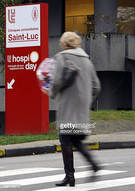 A woman passes by a sign of the 'Cliniques Universitaires SaintLuc' where Belgian King Albert underwent a minor surgery in Brussels on November 17...