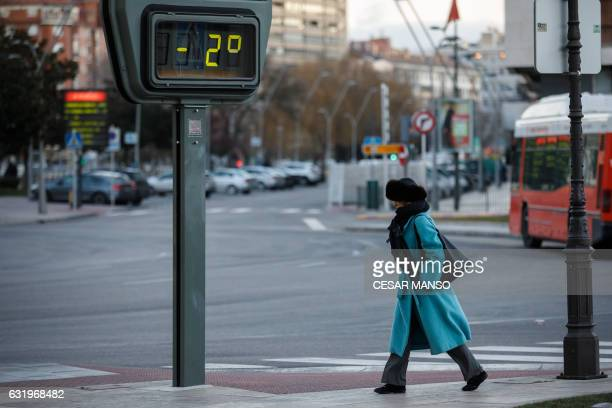 A woman passes by a thermometer displaying 2 degrees below zero during a cold winter day on January 18 in the city of Burgos where temperatures are...