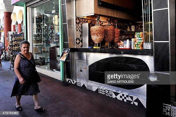 A woman passes by a traditional Greek fast food doner kebab shop in Thessaloniki on July 7 2015 European leaders warned Greek Prime Minister today to...