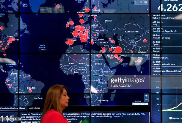 A woman passes by a world map showing countries infected with the new Coronavirus COVID19 during a press conference at the National Police...