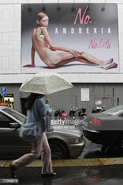 Woman passes by an italian advertising campaign featuring the photo of an emaciated girl, 26 September 2007 in Milan, in the middle of Milan fashion...