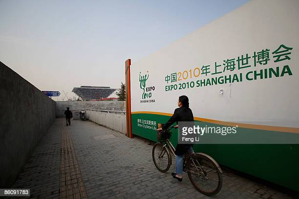 A woman passes by bike in front of the construction of the China Pavilion at the World Expo site on April 21 2009 in Shanghai China Expo 2010 is a...