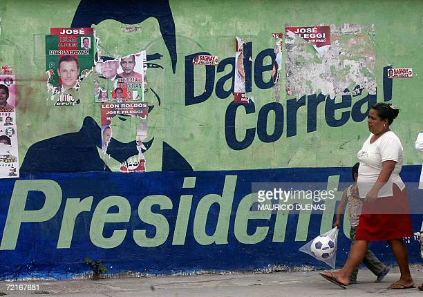 A woman passes by electoral propaganda of presidential candidate Rafael Correa 14 October in the town of Recreo Guayas province Ecuador Leftist US...