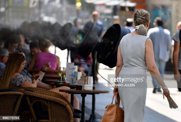 A woman passes by fans spraying water on clients on the terrace of the bar of the Circulo de Bellas Artes building during a heatwave in Madrid on...