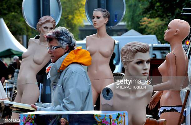 A woman passes by items on sale during the annual Braderie de Lille on September 1 2012 in Lille northern France At least two million visitors are...