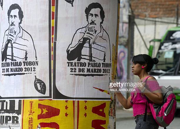 Woman passes by posters with the image of deceased Colombian drug lord Pablo Escobar along a street of Medellin, Antioquia department, Colombia, on...