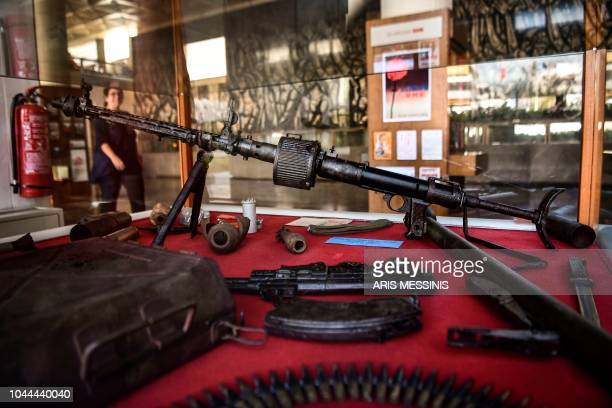 A woman passes by relics of Civil War weaponry in the hall of the Greek Communist party compound in Athens on September 26 2018 The Greek Communist...