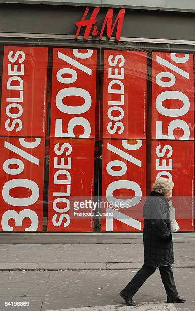 A woman passes by 'Sales' posters of the window display of HM department store during the official start of the 2009 winter sales on January 7 2009...