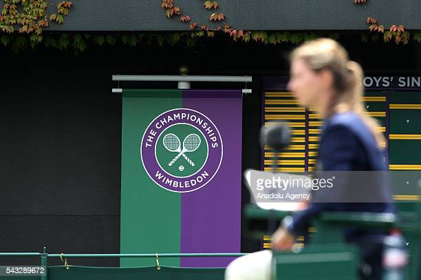 A woman passes by the logo of Wimbledon on day one of the 2016 Wimbledon Championships at the All England Lawn Tennis and Croquet Club in London...
