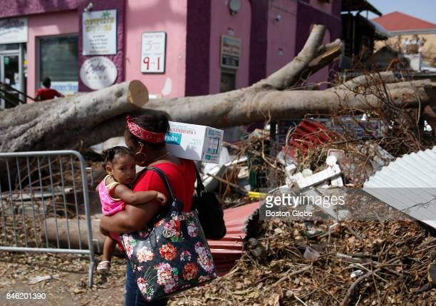 A woman passes debris from Hurricane Irma strewn in Cruz Bay on St John in the US Virgin Islands on Sept 12 2017 The island was hit hard by Hurricane...