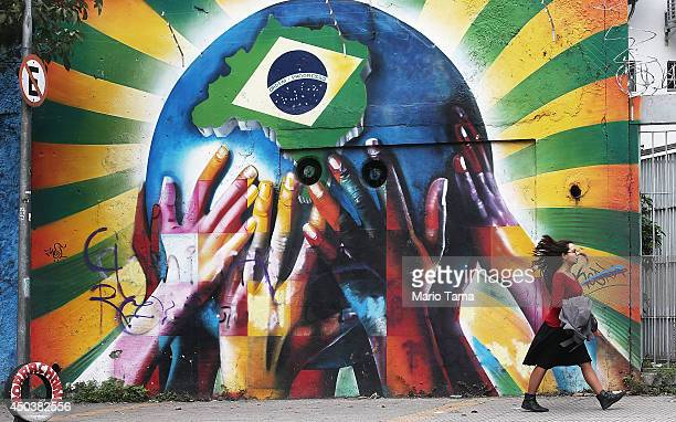 A woman passes graffiti of multicolored hands supporting the planet marked with a Brazilian flag on June 10 2014 in Sao Paulo Brazil The opening...