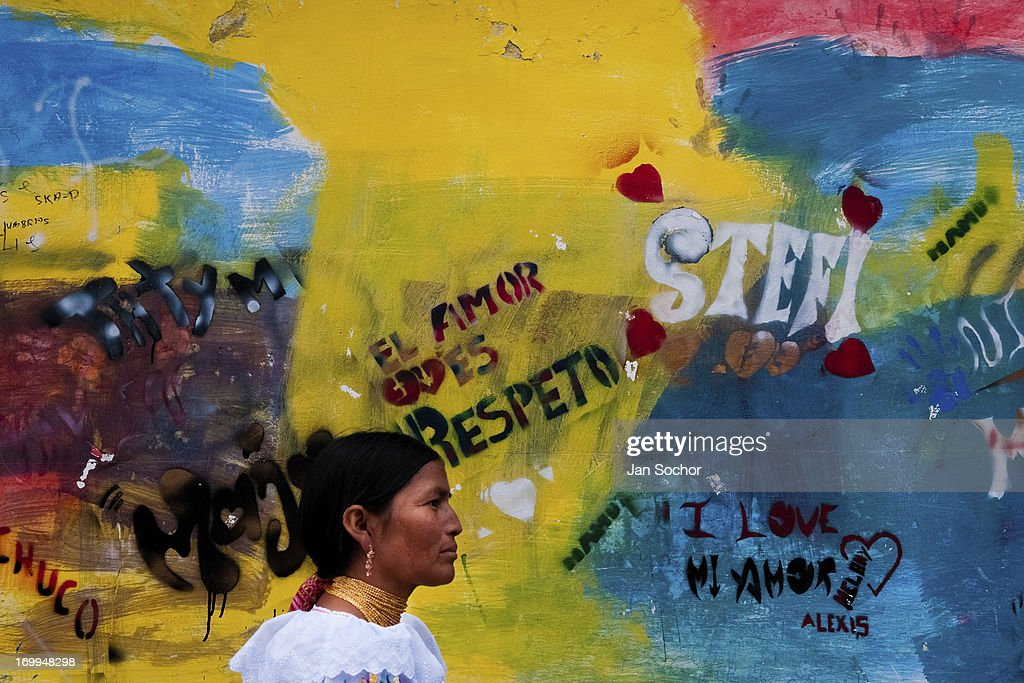 "A woman passes in front of a colorfully paited wall during the Inti Raymi fiesta on 29 June 2010 in Cotacachi, Ecuador. Inti Raymi, ""Festival of the Sun"" in Quechua language, is an ancient spiritual ceremony held in the Indian regions of the Andes, mainly in Ecuador and Peru. The lively celebration, set by the winter solstice, goes on for various days. The highland Indians, wearing beautiful costumes, dance, drink and sing with no rest. Colorful processions in honor of the God Inti (Sun) pass through the mountain villages giving thanks for the harvest and expressing their deep relation to the Mother Earth (Pachamama)."