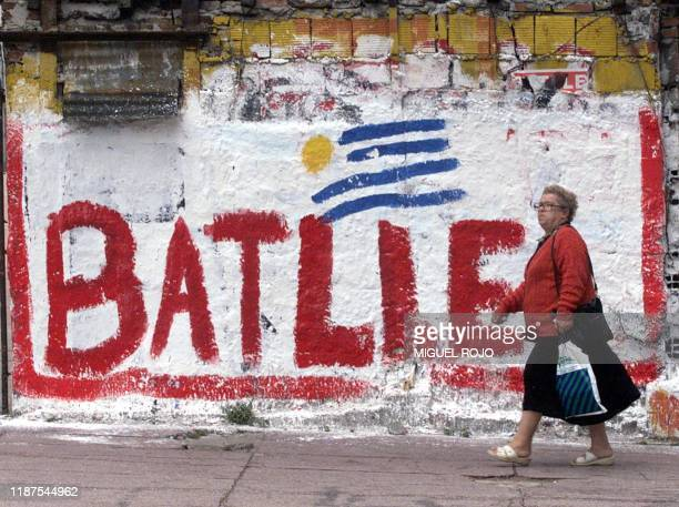 A woman passes in front of a wall that advertises the election of Jorge Batlle a presidential candidate for the Colorado Party Montevideo Uruguay 22...
