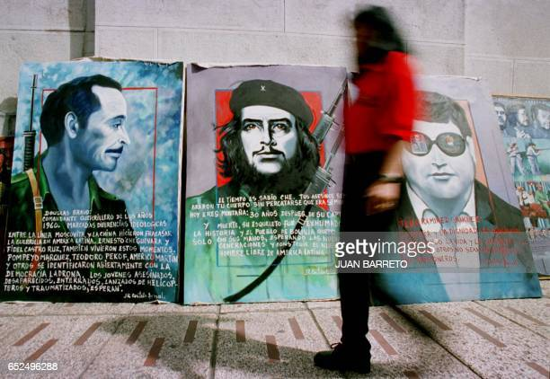 Woman passes in front of the paintings of Ernesto Ché Guevara, Venezuelan guerrilla Brave Douglas and Venezuelan Carlos Ilich Ramirez Sanchez,...