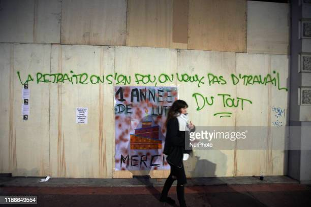 Woman passes near a graffiti reading 'We don't care for retirement, we don't want to work at all'. Between 60 and 80000 protesters took to the...
