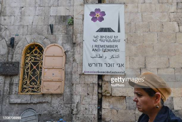 A woman passes near 'Armenian Genocide Centennial' poster in the Armenian Quarter of the Old City of Jerusalem On Wednesday March 11 in Jerusalem...