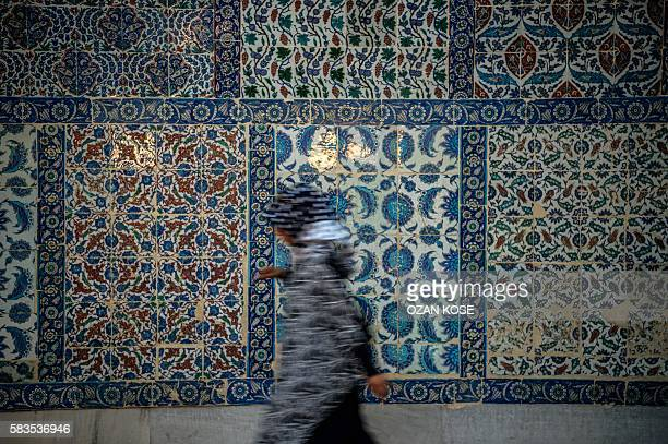 TOPSHOT A woman passes next to a traditional tile wall at Eyup sultan mosque on July 26 2016 at Eyup district in Istanbul following the failed...