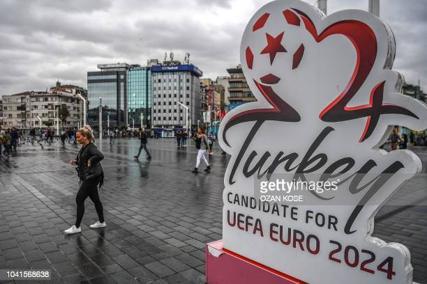 A woman passes next to a Turkey's Euro 2014 logo at Taksim square in Istanbul on September 27 2018 UEFA will select the host of the 2024 European...