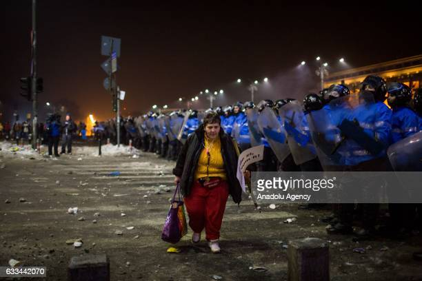 A woman passes Romanian riot police during a protest against the new Romanian government's passing of an executive order to pardon prisoners during a...