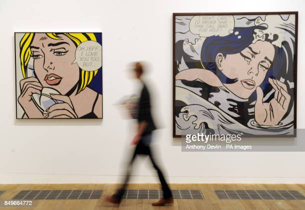 A woman passes Roy Lichtenstein's paintings OhJeffI Love You TooBut 1964 and Drowning Girl during the press preview for Lichtenstein A Retrospective...