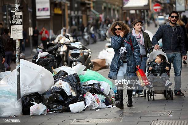 A woman passes rubbish piled up in the central street on November 19 2010 in Naples Italy Around 2000 tons of rubbish have accumulated in various...