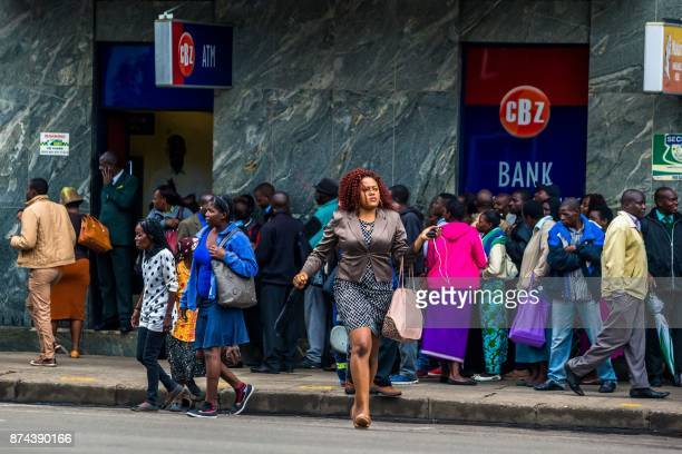 A woman passes the street as Harare residents queue outside a bank in Harare on November 15 2017 Zimbabwe's military appeared to be in control of the...
