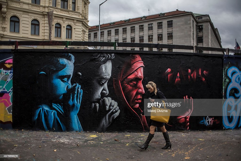 A woman passes the wall with graffiti to honour the victims of the Paris terrorist attacks by the Kazakhstani artist called ChemiS on November 18, 2015 in Prague, Czech Republic. People across the world commemorate the victims of the attacks last Friday in Paris that left 130 people dead across the French capital.