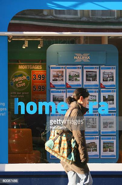 A woman passes the window of a branch of Halifax estate agents on March 3 2008 in Bath United Kingdom Banks and building societies in the UK are...