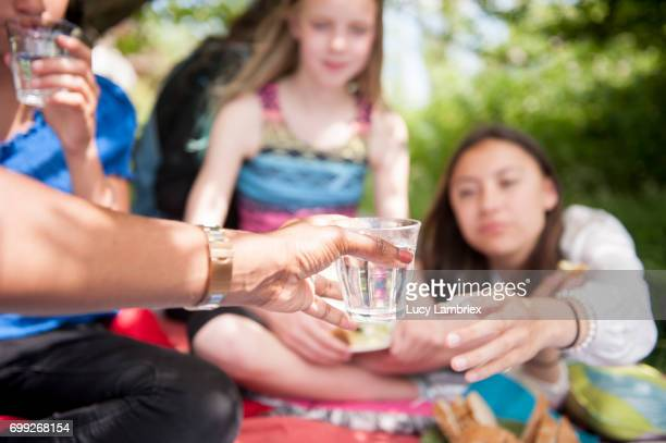 Woman passing a glass of water at a picnic with girls and women