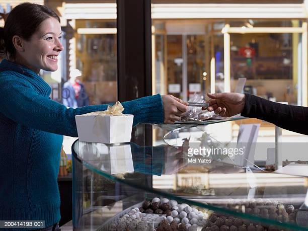 Woman passing bank card across counter in chocolate shop, smiling
