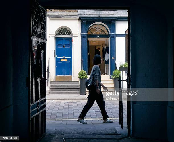 woman passing by - black alley stock photos and pictures
