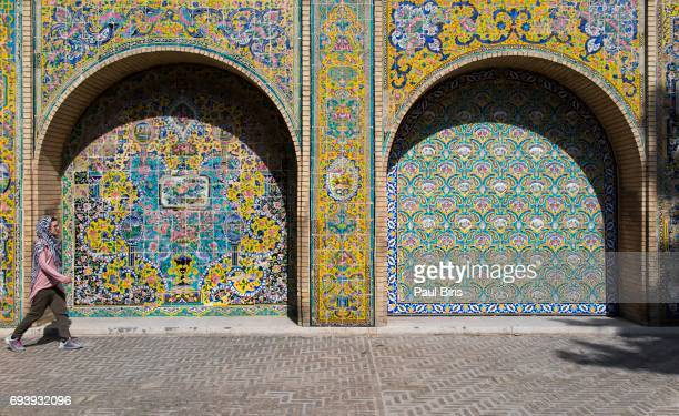 Woman passing near the Tiled walls of the Golestan Palace in Tehran, Iran.