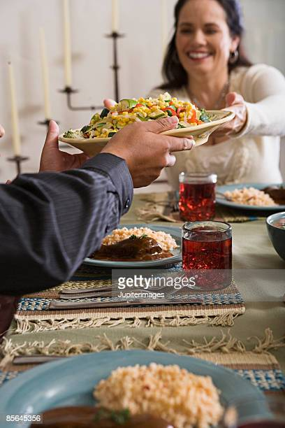 woman passing plate of food - mole sauce stock pictures, royalty-free photos & images
